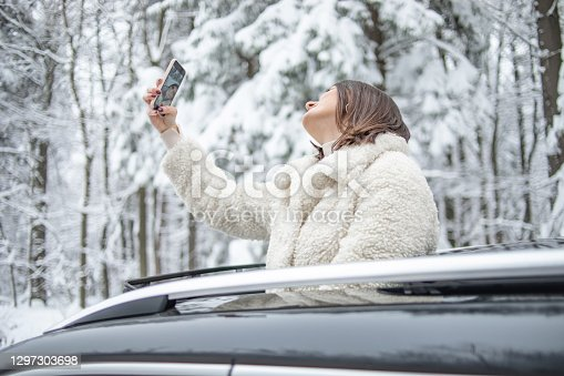 Beautiful happy woman in warm clothes enjoys a beautiful winter day as she travels through a snow-covered forest