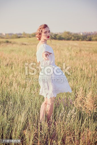 Beautiful young woman is saying goodbye and leaving. Portrait in a meadow