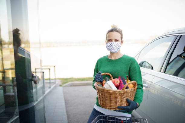 beautiful young woman is shopping with mouth protecting mask during corona stock photo