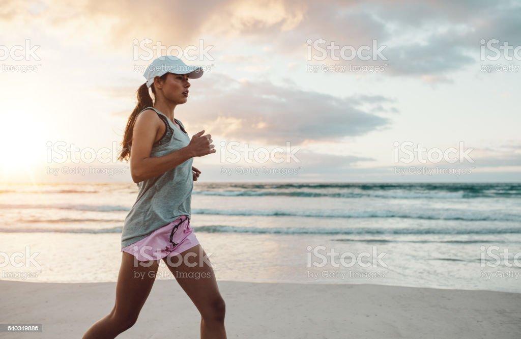Beautiful young woman jogging on beach stock photo