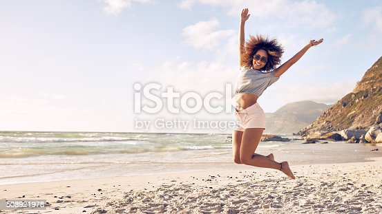 istock Beautiful young woman jumping at the beach 508921978