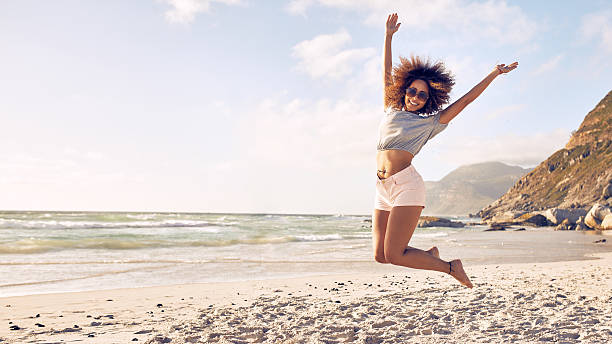 Beautiful young woman jumping at the beach stock photo