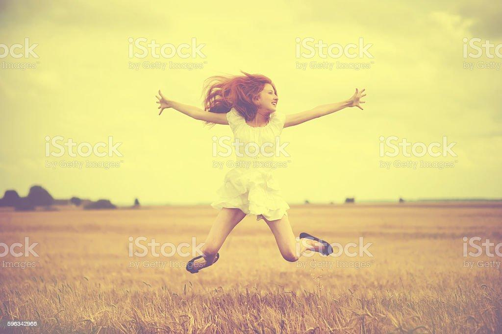 Beautiful young woman jumping at wheat field royalty-free stock photo