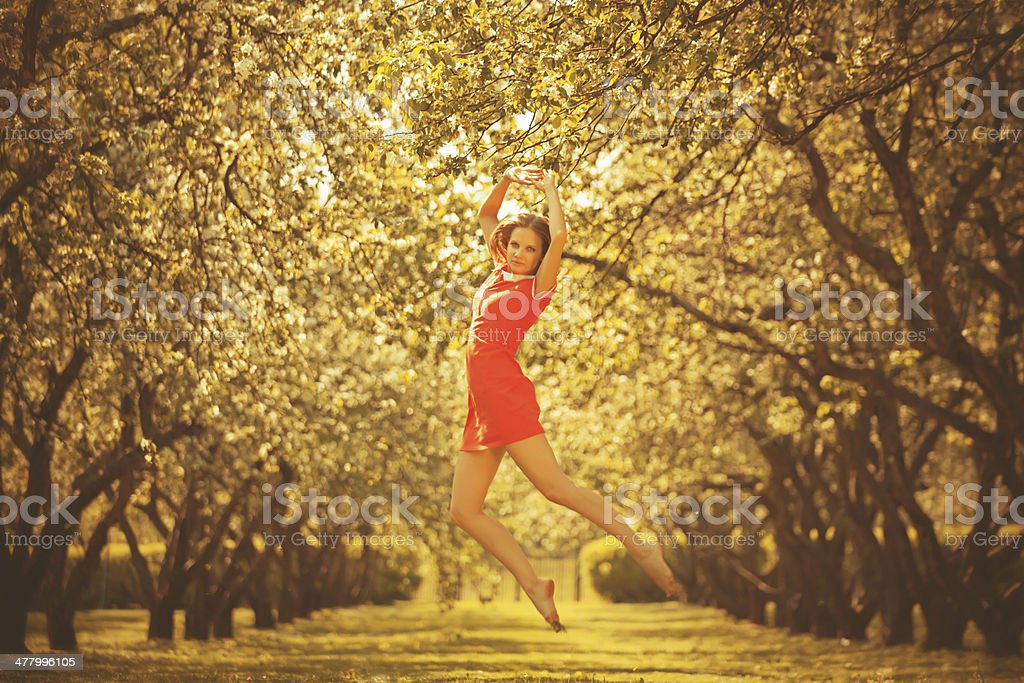 Beautiful young woman jumping in park royalty-free stock photo