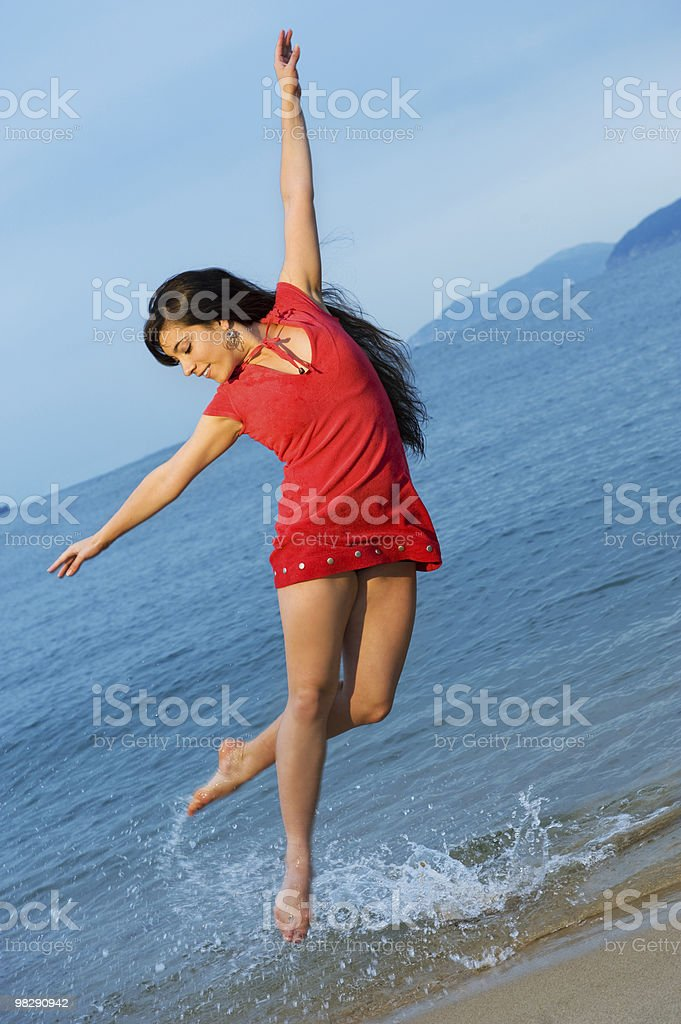 Beautiful young woman jumping in the sea royalty-free stock photo