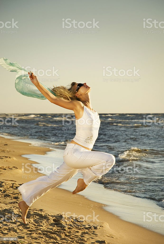 Beautiful young woman jumping on a beach at sunset royalty-free stock photo
