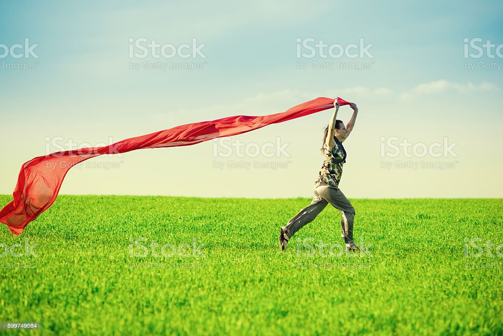 Beautiful young woman jumping on a green meadow with colored stock photo