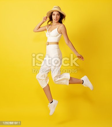 Beautiful young woman jumping with straw hat in white dress front of yellow background.