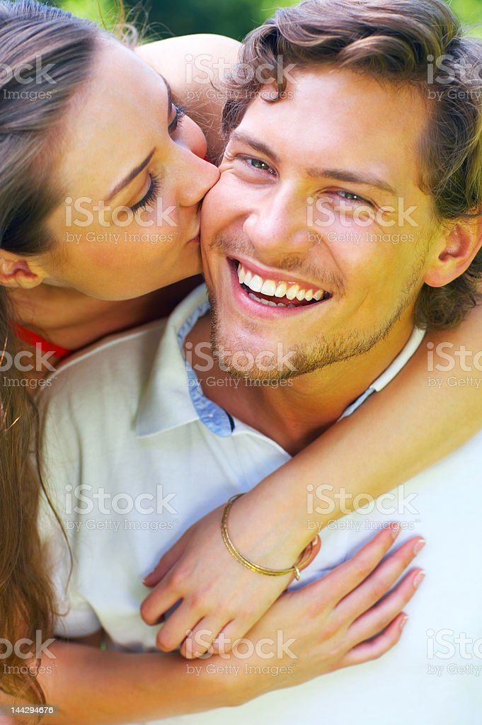 Beautiful young woman kissing her boyfriend royalty-free stock photo