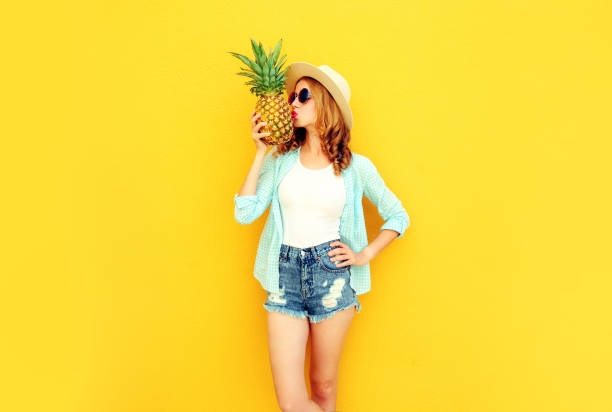 Beautiful young woman kissing pineapple in summer straw hat, shorts on colorful yellow background stock photo