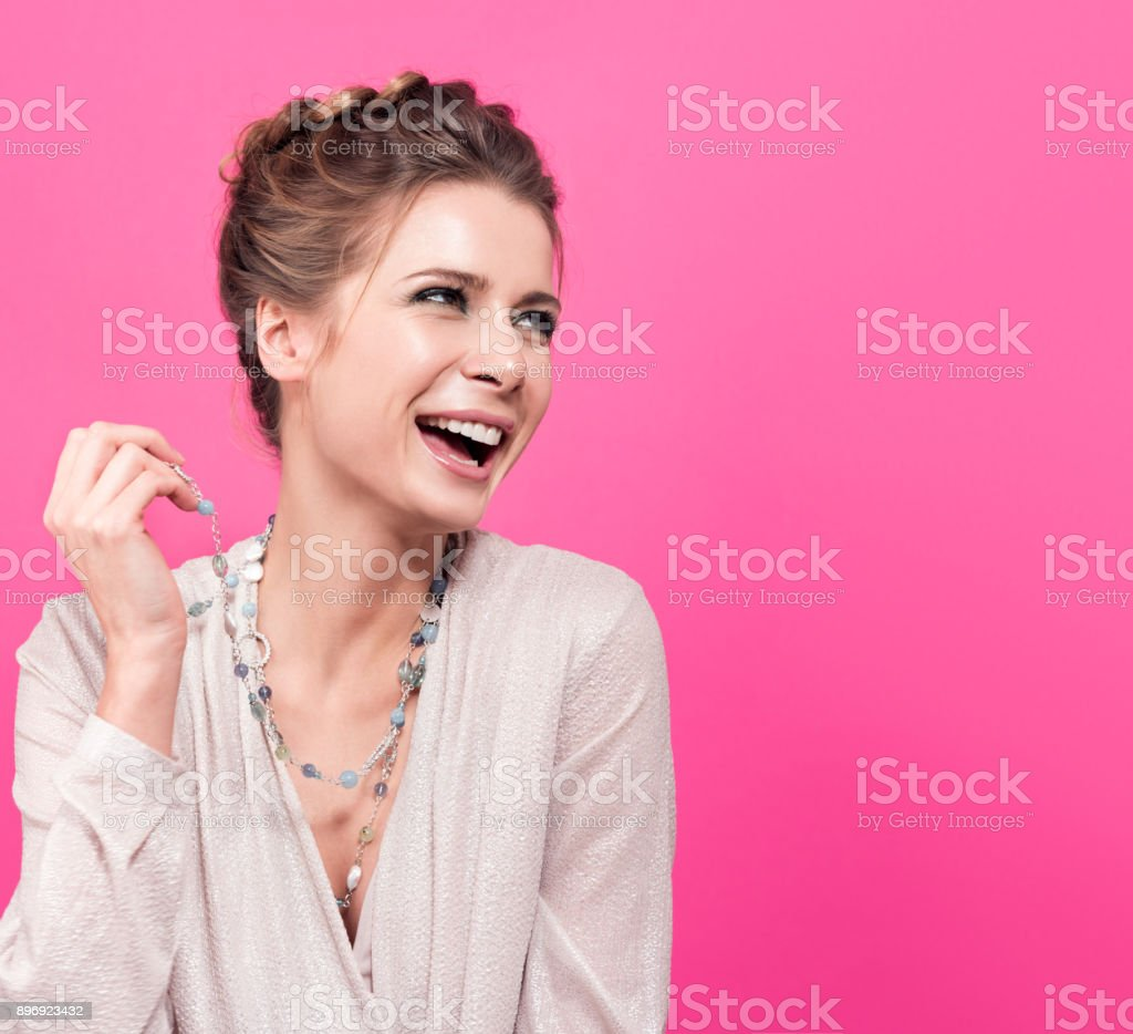 Beautiful young woman laughing. Long necklace on the neck, stylish appearance, hairstyle and nude makeup stock photo