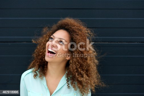 186534921 istock photo Beautiful young woman laughing outdoors and looking up 462918995