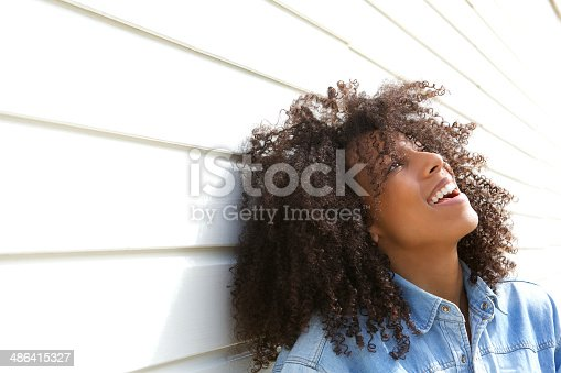 istock Beautiful young woman laughing outdoors 486415327