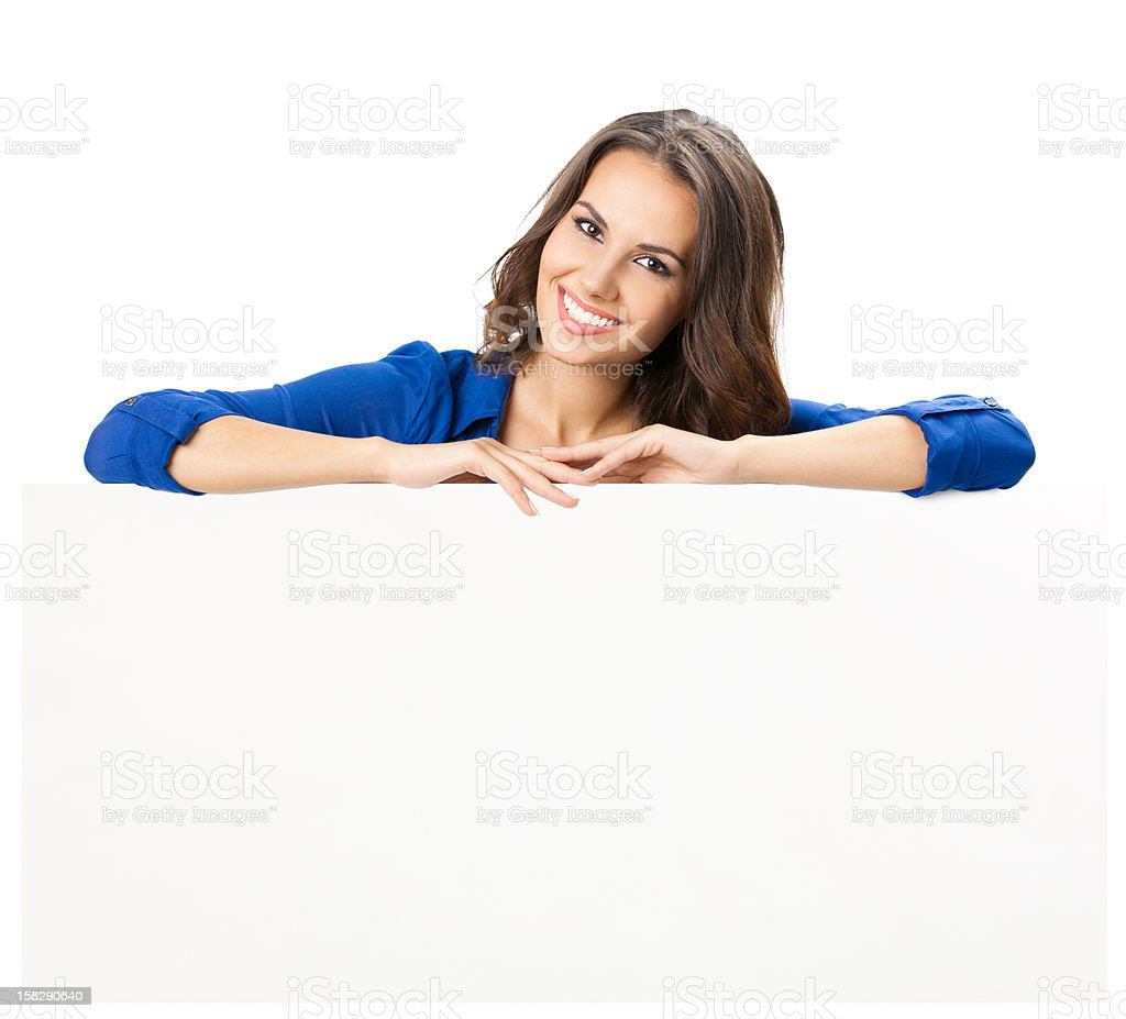 Beautiful young woman leaning against a blank white board stock photo
