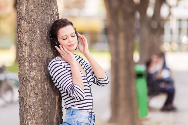 Beautiful young woman leaning on a tree and listening to a music outdoors stock photo