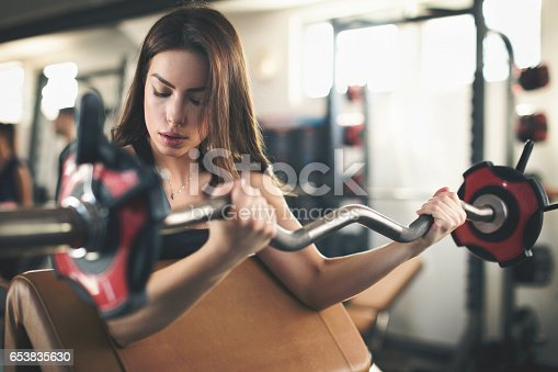 670937518istockphoto Beautiful young woman lifting weights 653835630