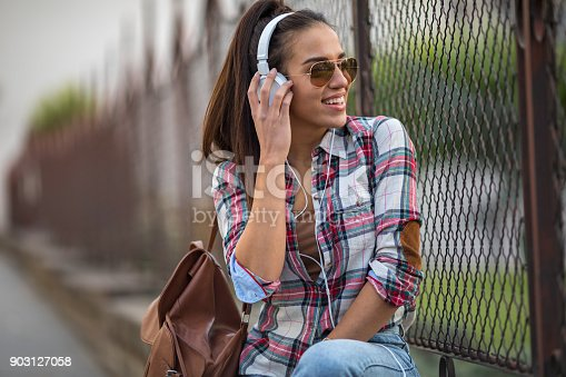 625928750 istock photo Beautiful young woman listening to music on the street 903127058