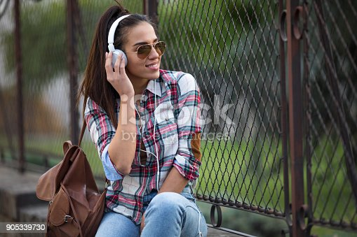 625928750 istock photo Beautiful young woman listening to music on the street 905339730