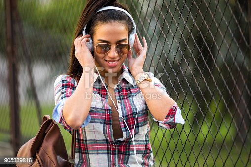 625928750 istock photo Beautiful young woman listening to music on the street 905339816