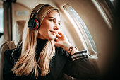 Young successful blonde woman sitting on a private jet and listening to music through headphones.