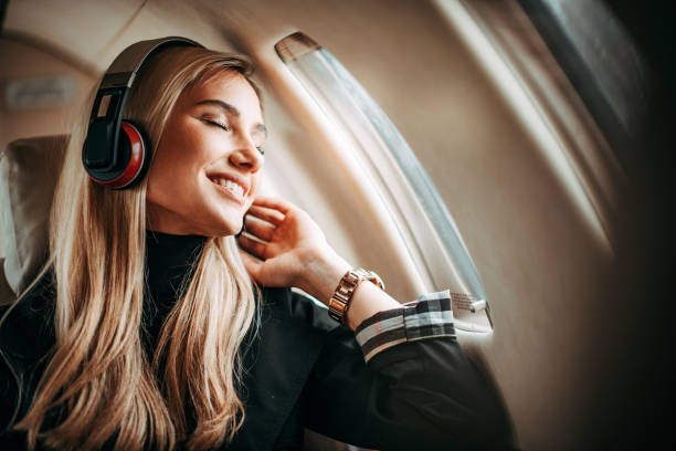 Beautiful young woman listening to music through the headphones in a private jet stock photo