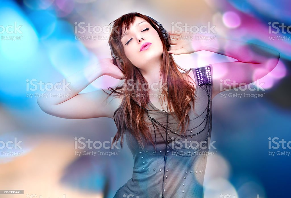 Beautiful young woman listening to music with headphones stock photo