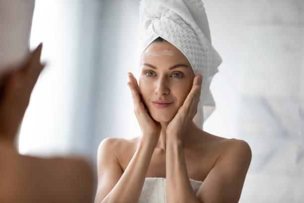 Schöne junge Frau Blick in Spiegel massieren Gesicht Anwendung Creme – Foto
