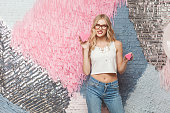 Beautiful young woman with blondie long hair in stylish glasses, looking at camera and holds two cookies in form of hearts. Isolated studio shot on colorful abstract background