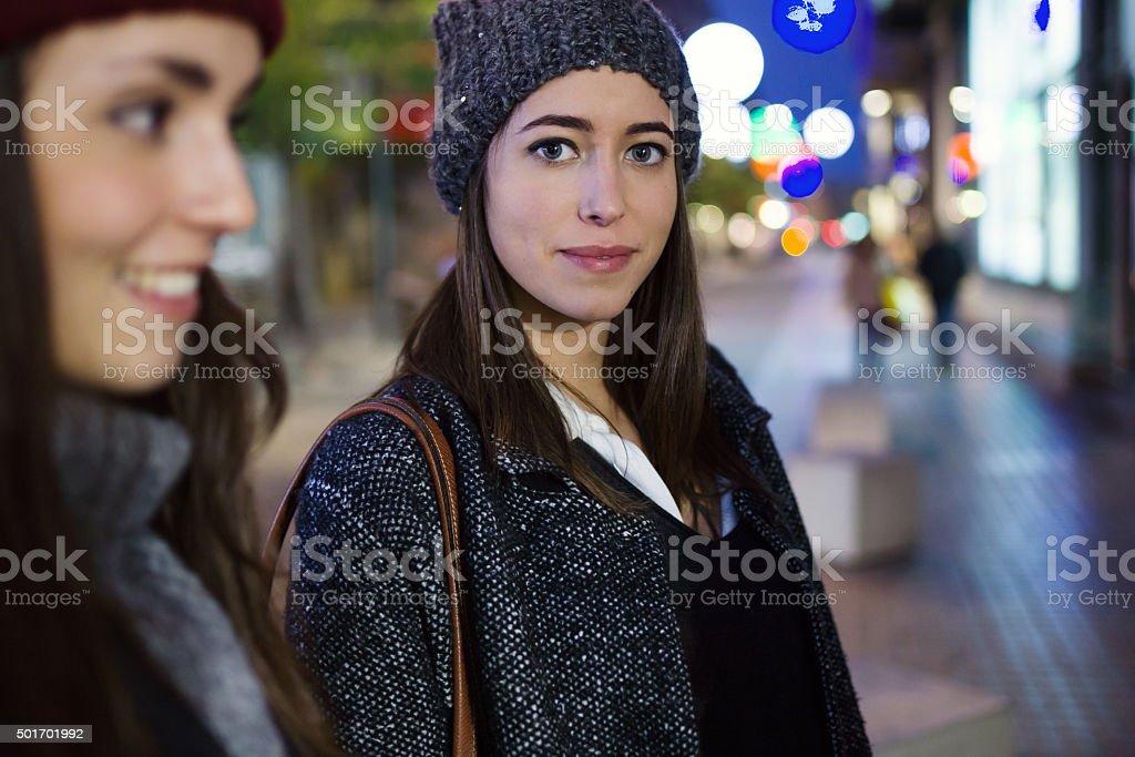 Beautiful young woman looking at camera at night. stock photo
