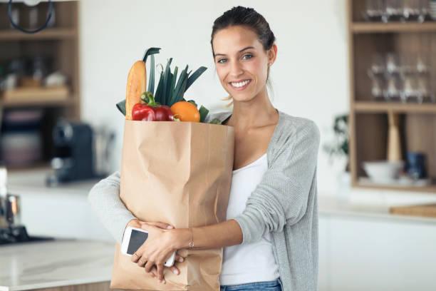 Schöne junge Frau schaut auf Kamera, während sie Einkaufstasche mit frischem Gemüse in der Küche hält. – Foto