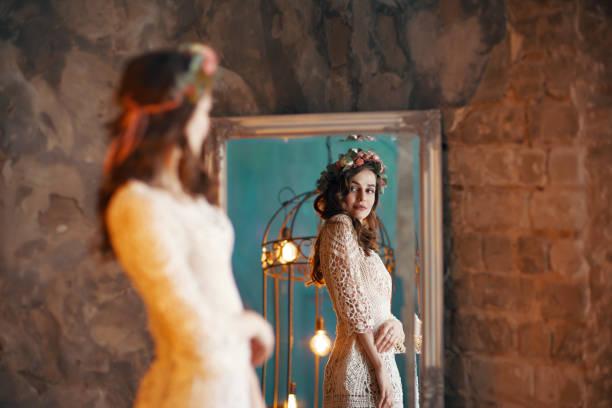 Hermosa jovencita mirando su reflejo en el espejo - foto de stock