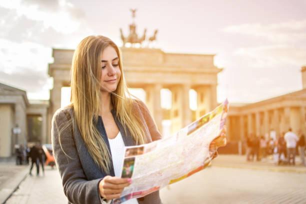 Schöne junge Frau Karte Führer stehen im Vordergrund des Brandenburger Tors bei Sonnenuntergang zu betrachten. – Foto