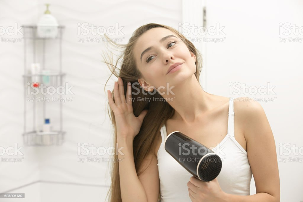 Beautiful young woman looking at the mirror drying hair stock photo