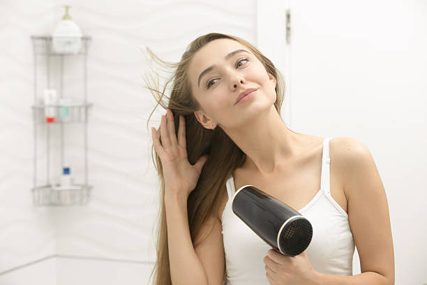 beautiful young woman looking at the mirror drying hair - beautiful curvy girls stock photos and pictures