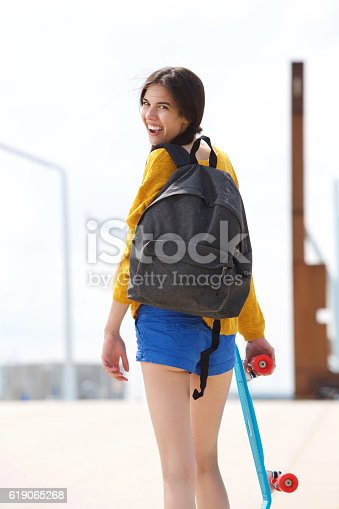 istock Beautiful young woman looking back with skateboard 619065268