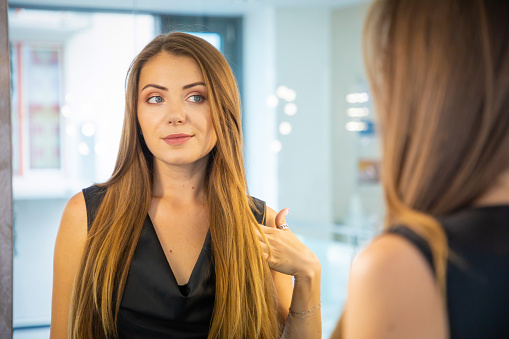 istock Beautiful young woman looking in the mirror 1035625276