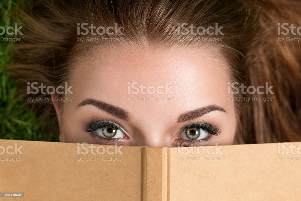 Beautiful young woman looking over book cover stock photo