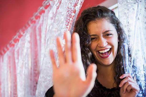 schöne junge frau, die durch einen vorhang - lange duschvorhänge stock-fotos und bilder