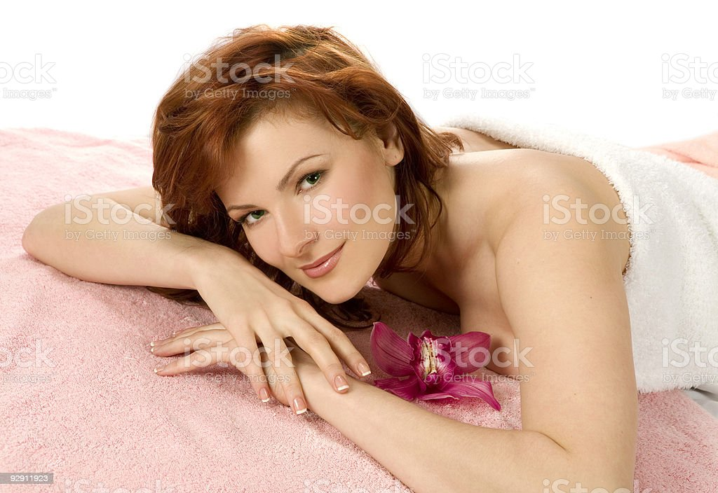 Beautiful young woman lying down for massage  with orchid. royalty-free stock photo