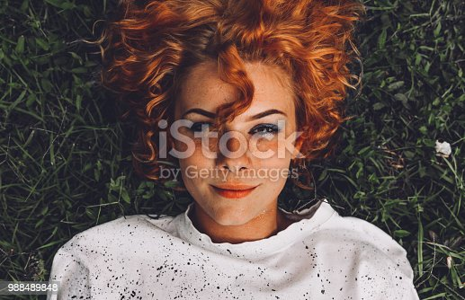 istock Beautiful young woman lying down in the grass 988489848