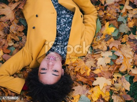 istock Beautiful young woman lying in autumn leaves 477548605
