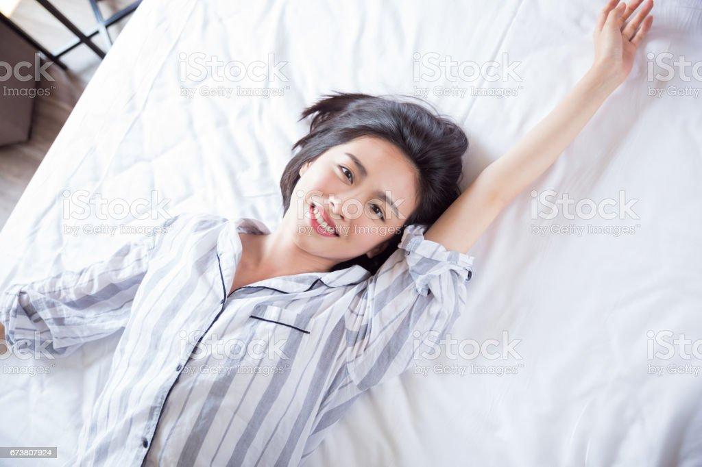 Belle jeune femme allongée sur le lit photo libre de droits