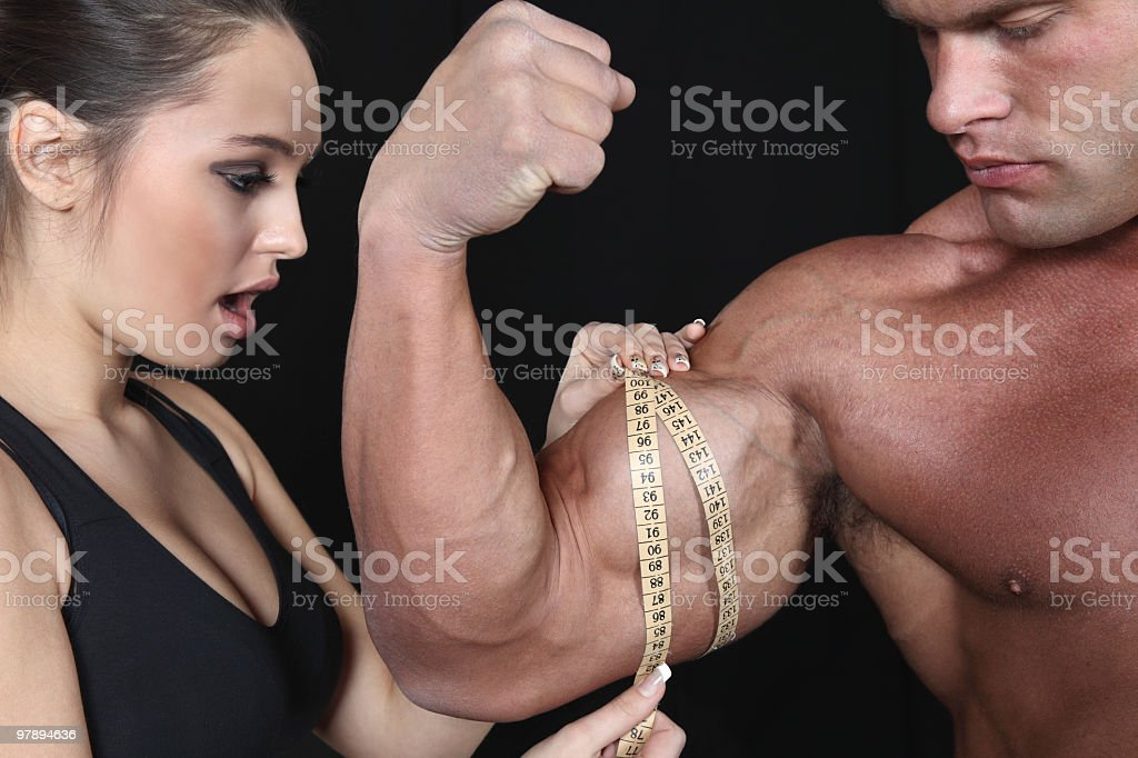Beautiful young woman measuring male's biceps royalty-free stock photo