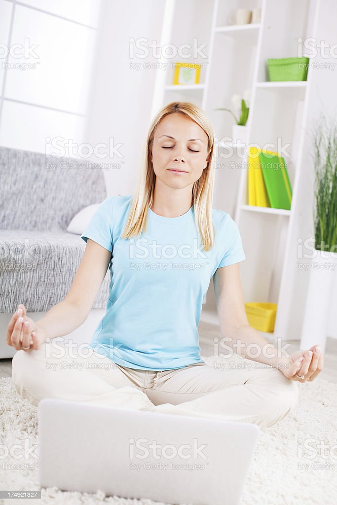 Beautiful young woman meditating in the living room royalty-free stock photo