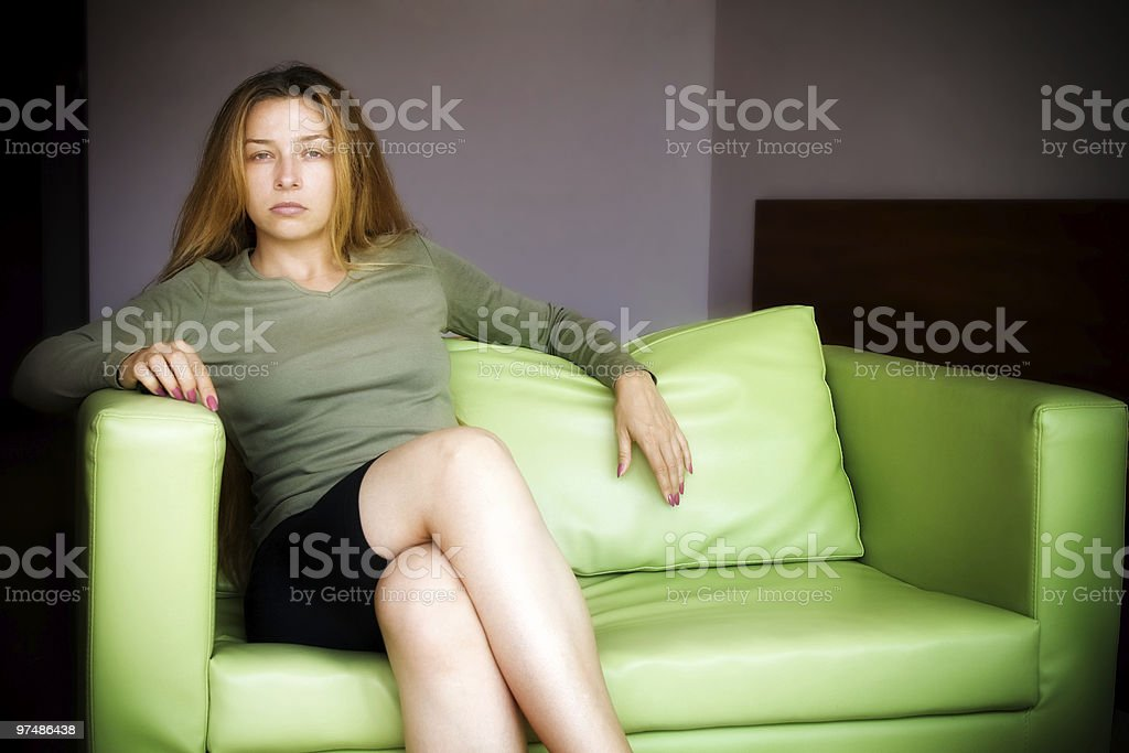 Beautiful young woman on green couch royalty-free stock photo