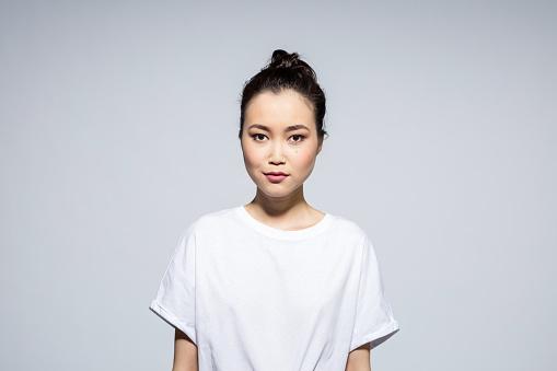 Portrait of beautiful asian young woman wearing white t-shirt, looking at camera. Studio shot, grey background.