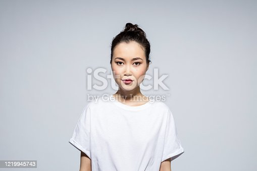 Portrait of beautiful asian young woman wearing white t-shirt, looking at camera. Studio shot, grey background.