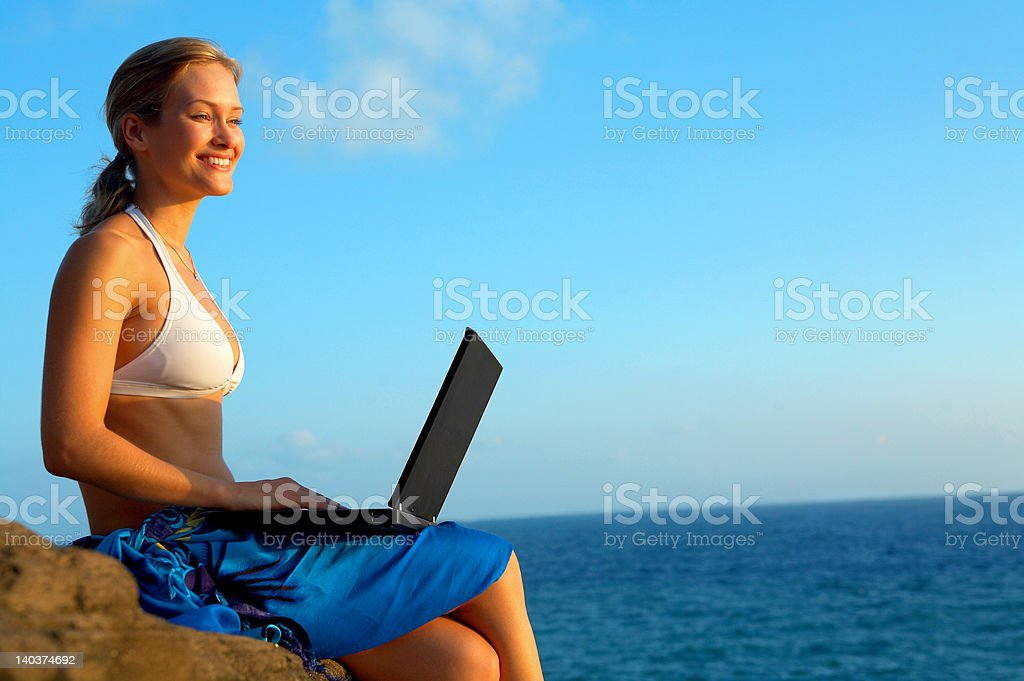 Beautiful young woman on the beach with laptop royalty-free stock photo