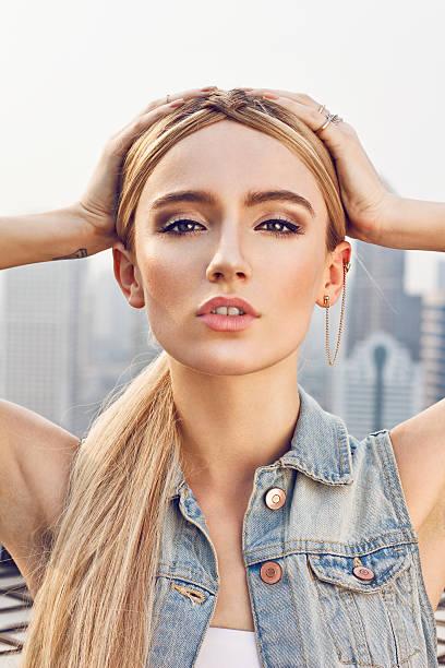 schöne junge frau auf dem dach - damen top gold stock-fotos und bilder
