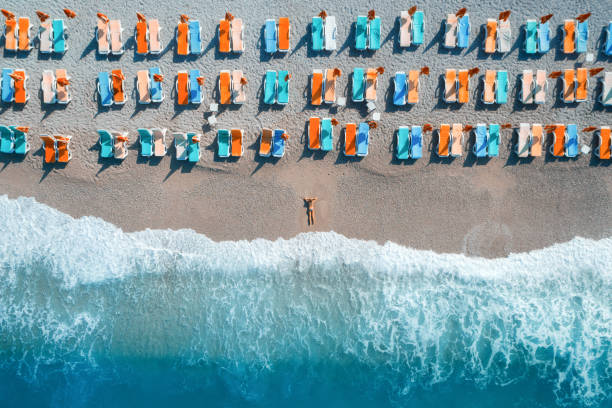 Beautiful young woman on the sea at sunrise in Oludeniz, Turkey. Aerial view of lying woman on the beach with colorful chaise-lounges. Top view from drone. Seascape with girl, azure water and waves stock photo